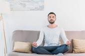 Photo handsome man with eyes closed sitting on couch in Lotus Pose and meditating at home