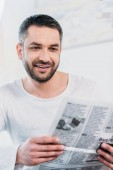 selective focus of handsome smiling man reading newspaper at home