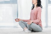 Photo Cropped view of woman in Lotus Pose practicing meditation at home in Living Room