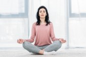 Photo beautiful woman with eyes closed in Lotus Pose practicing meditation in Living Room at home