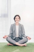 Photo beautiful smiling businesswoman in suit meditating while sitting on grass mat in Lotus Pose