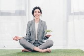 beautiful smiling businesswoman sitting on grass mat in Lotus Pose, meditating and holding flowerpot