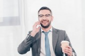 handsome smiling businessman in glasses and suit with coffee to go talking on smartphone