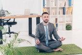 businessman sitting on grass mat in Lotus Pose and meditating in office