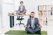 businessman meditating on grass mat while businesswoman sitting on table in Lotus Pose in office