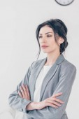 beautiful serious businesswoman in suit with crossed arms looking away