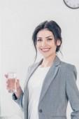 schöne lächelnde Geschäftsfrau im Anzug hält ein Glas Wasser in der Hand und schaut in die Kamera