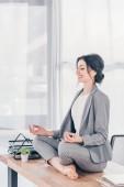 krásná usměvavá podnikatelka v obleku meditující na stole v Lotus Pose v úřadu