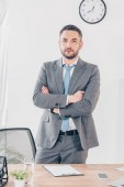 serious handsome businessman in suit with crossed arms looking at camera in office