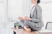 vágott kilátás üzletasszony a ruha ül az asztalon, és meditál a Lotus Pose hivatalban