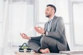 schöner Geschäftsmann mit geschlossenen Augen meditiert in Lotus-Pose auf Bürotisch