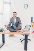 Fotografie stattliche Geschäftsmann im Anzug meditieren in Lotus Pose, während auf Büroschreibtisch sitzen