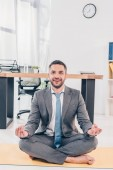 handsome smiling businessman meditating in Lotus Pose on fitness mat in office