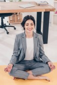 beautiful smiling businesswoman in suit meditating in Lotus Pose in office