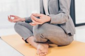 partial view of businesswoman in suit sitting in Lotus Pose on fitness mat and meditating in office