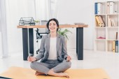 beautiful smiling businesswoman in suit sitting on fitness mat and meditating in office