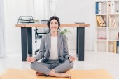beautiful smiling businesswoman in suit sitting on fitness mat, looking at camera and meditating in office