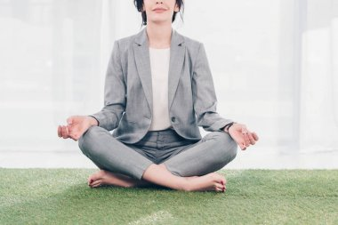 Cropped view of businesswoman in suit meditating while sitting on grass mat in Lotus Pose stock vector