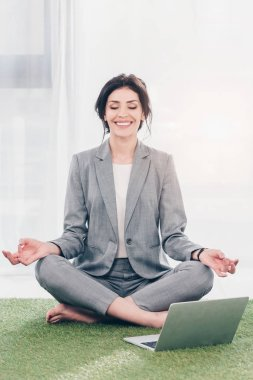 smiling businesswoman in suit meditating while sitting on grass mat in Lotus Pose near laptop