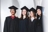 group of cheerful students in graduation caps smiling in university