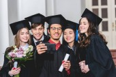 cheerful group of students in graduation caps talking selfie on smartphone