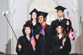 cheerful students in graduation gowns holding flags of different countries and taking selfie on smartphone