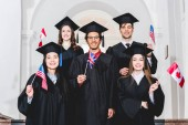 happy students in graduation gowns holding flags of different countries
