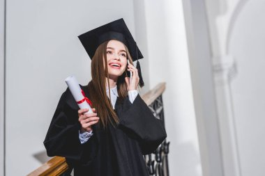 low angle view of cheerful young woman holding diploma while talking on smartphone