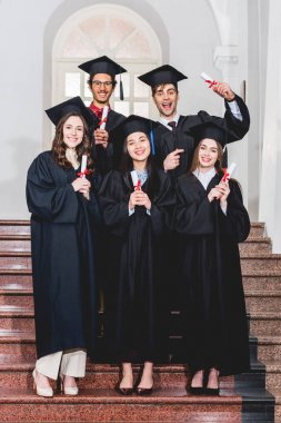 cheerful group of students in graduation gowns holding diplomas