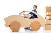 Fotografie chlapec sedící v lepenkovém autě a přidržením volantu na bílém
