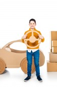 Fotografie boy near cardboard car holding steering wheel and looking at camera on white