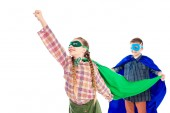 boy holding cape of smiling kid in superhero costume posing with outstretched hand isolated On White