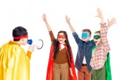 Fotografie happy kids in superhero costumes raising hands while boy shouting in mouthpiece Isolated On White