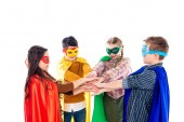 kids in superhero costumes and masks Stacking Hands Isolated On White
