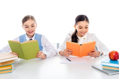 schoolgirls in formal wear sitting at desk and reading books Isolated On White