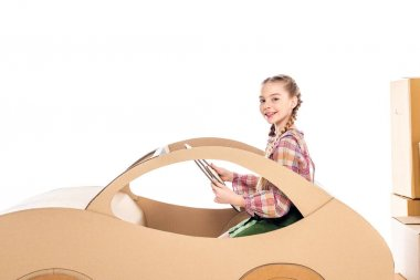 Happy kid looking at camera and holding steering wheel while playing with cardboard car Isolated On White stock vector