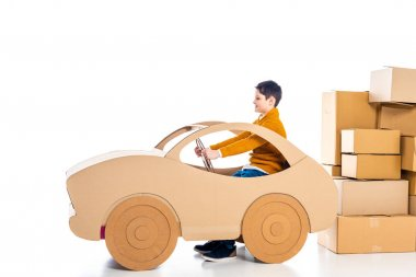 Boy sitting and playing with cardboard car near packages on white with copy space stock vector