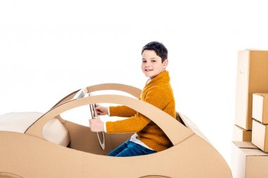 Boy looking at camera, sitting and playing with cardboard car near packages Isolated On White stock vector