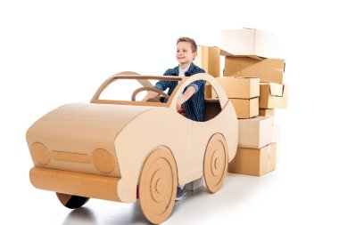 Happy boy playing with cardboard car on white stock vector