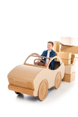 Happy boy playing with cardboard car on white with copy space stock vector