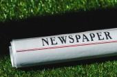 közelről hengerelt újság a zöld fű árnyék