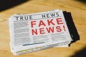 hromada novin s falešnými a pravými zprávami o dřevěném stole