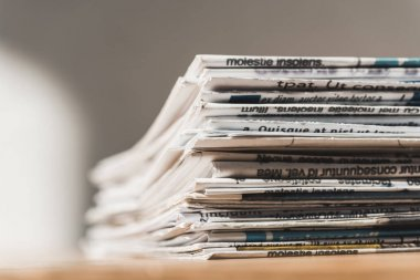 selective focus of different print newspapers in pile on wooden table