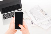 selective focus of woman holding smartphone with blank screen near laptop and  newspapers
