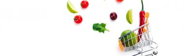 panoramic shot of scattered fruits and vegetables near decorative shopping cart isolated on white