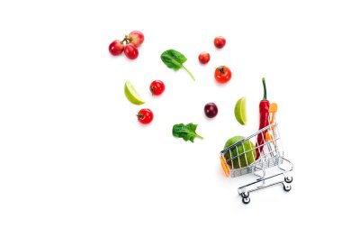 scattered fruits and vegetables near decorative shopping cart isolated on white