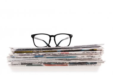 stack of daily newspapers with glasses on top isolated on white