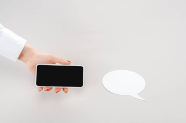 Cropped view of woman holding smartphone with blank screen near empty paper cut speech bubble stock vector