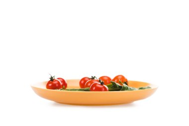 cherry tomatoes with green spinach leaves in yellow plate isolated on white