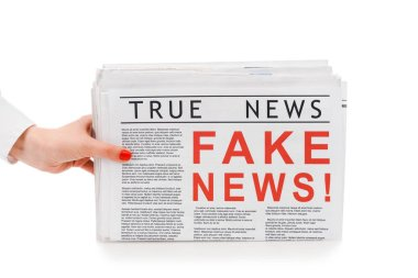 partial view of woman holding pile of newspapers with fake and true news isolated on white